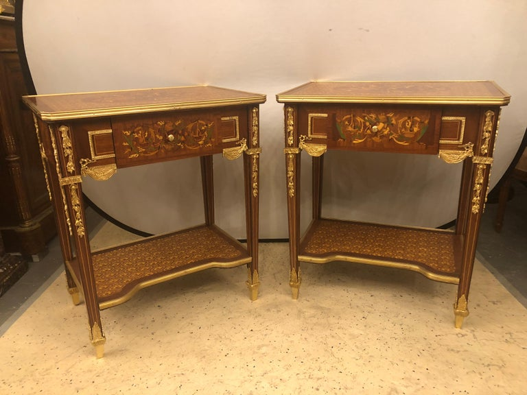 Pair of 19th-20th century Louis XVI style end or lamp tables that can be used as bedroom nightstands with bronze mounts and inlaid drawers. Each of these fine custom quality designer end tables have too much style and grace to mention it all. The