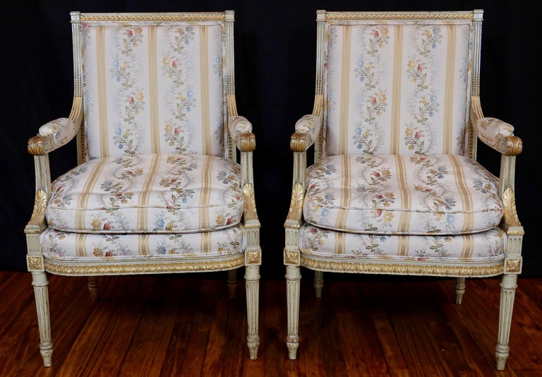 Pair of lovely Louis XVI style painted fauteuils with elegant silk lampas French fabric and double welt (early 20th century). The chairs are a light cream color with parcel gilt accents. Carved neoclassical ornaments include acanthus leaves, pearl