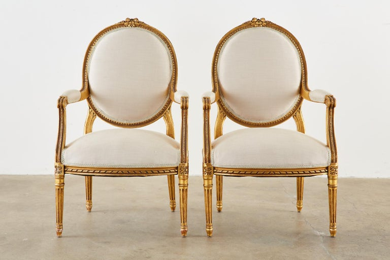 Stunning pair of late 19th century French fauteuil armchairs made in the grand Louis XVI taste. The chairs feature fine, highly carved giltwood frames embellished with rope, bead, and rosette decoration and topped with floral ribbon crests on the