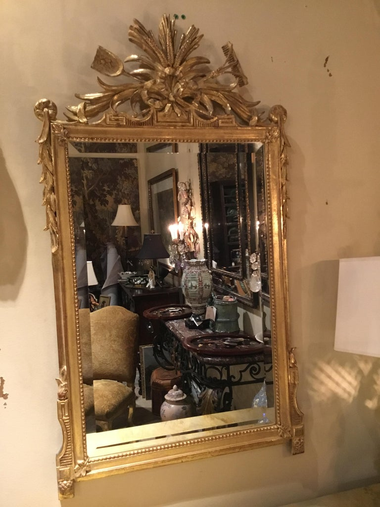 Pair of giltwood mirrors having a crest decorated with sheaves of wheat and garden Trophies tied with bow knots, the sides with trailing leaves, the lower sides with pine cone carved Feet, the molded surrounds with beaded liners, each set with a