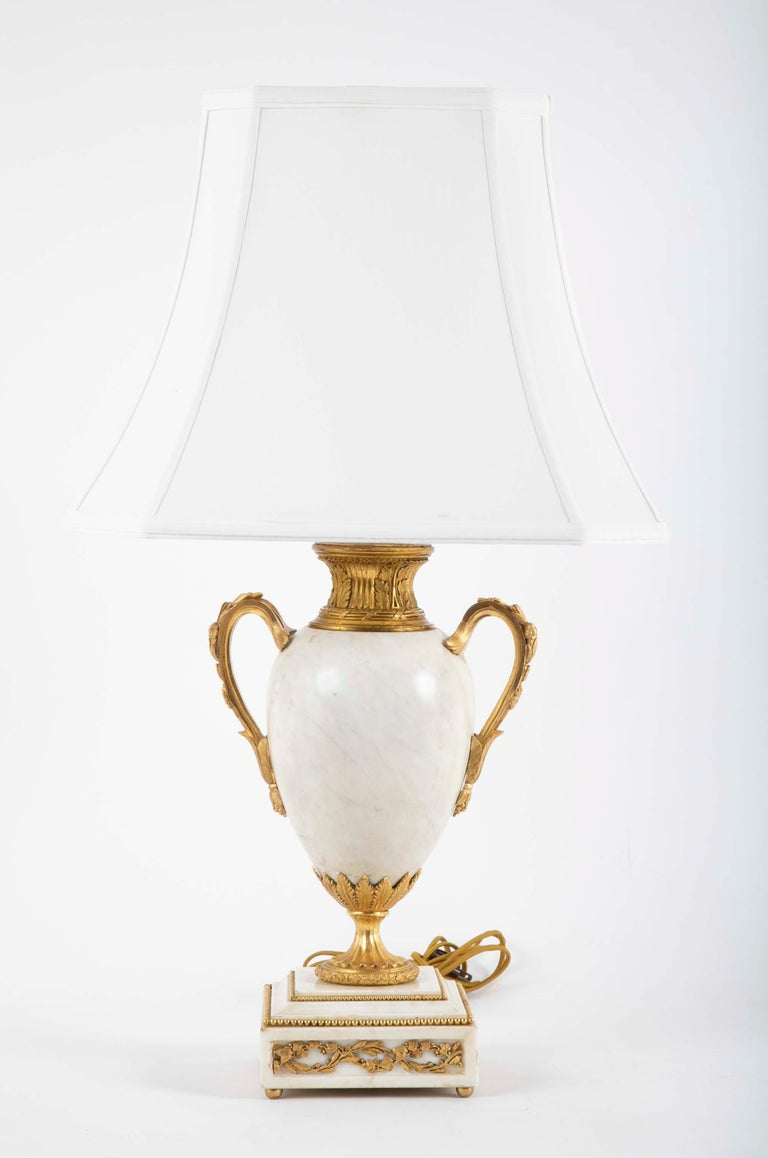 Pair of Louis XVI style ormolu mounted lamps with baluster form white marble vases on square marble base..   Provenance: Christie's, New York, 2003.