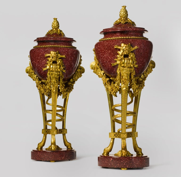 A pair of Louis XVI style gilt bronze mounted porphyry urns, after the Model by Pierre Gouthière.