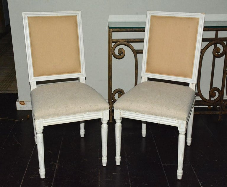 Pair of French Louis XVI style side dining chairs with wood frames in white painted finish, fluted leg and cubic blocks decorated with florets. Appropriate for dining or desk chairs in modern of traditional Swedish Gustavian Style decor.
