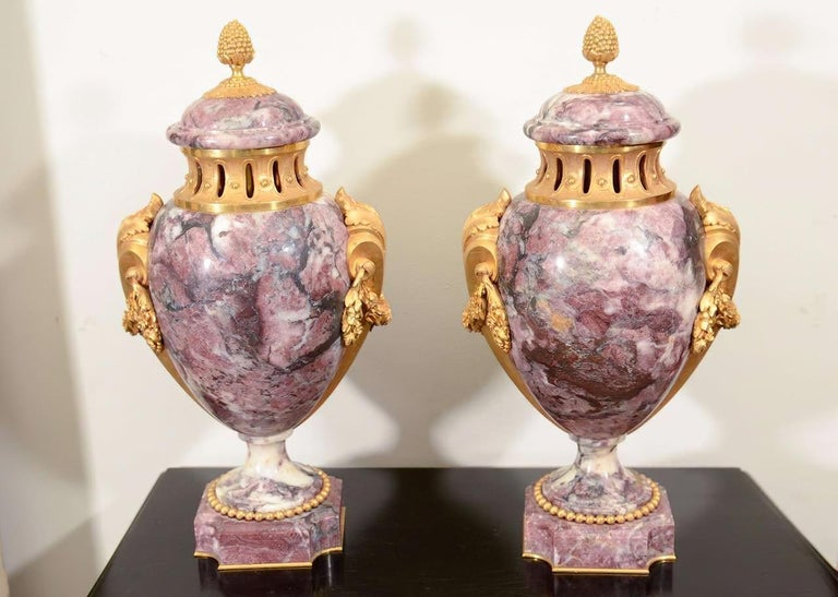 A pair of signed Louis XVI style marble and bronze covered urns with leaf form handles and floral drapery. Signed