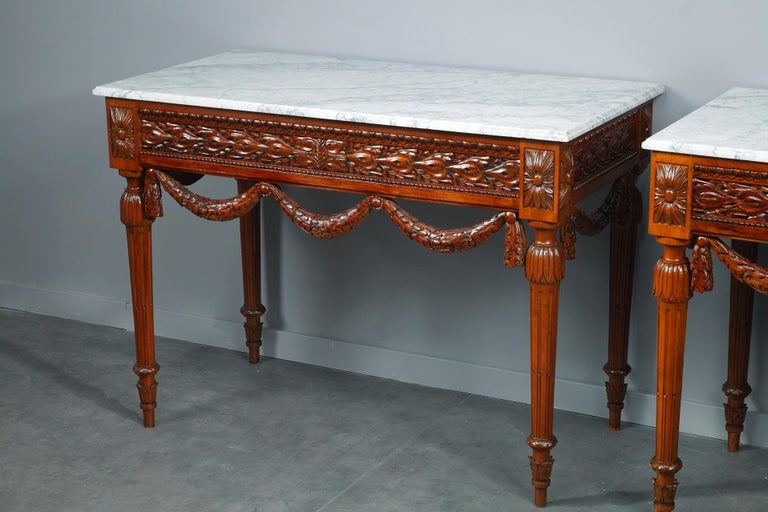 Pair of Louis XVI-style consoles tables crafted of walnut with white marble top. Crafted with a meticulous attention to detail, these tables epitomize the best elements of Louis XVI refined style: openwork foliage, garland of oak leaves and pearls.