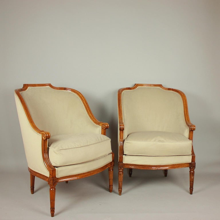 A pair of walnut bergeres or armchairs, each with a curved padded back. The top rail shaped to form a shallow arched and fluted top. The arm-rests descend to a spiral scroll to overlap the arm-supports, which sweep down again to meet the front legs.