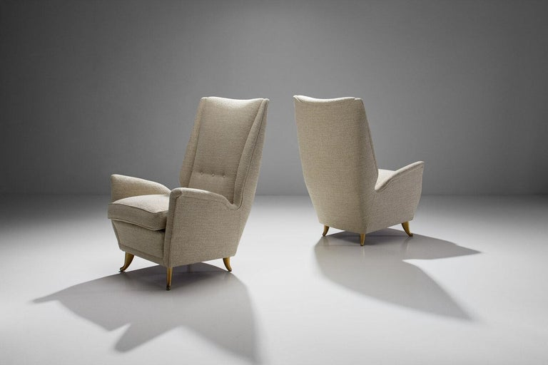 Pair of lounge chairs attributed to Gio Ponti for ISA Bergamo, Italy, 1950s  A pair of elegant high back chairs gracefully resting on four brass-colored metal curved feet. The strong lines and proportions of the chairs are perfectly balanced with