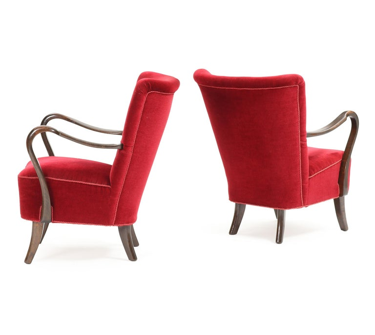 A pair of Danish modern easy chairs with stained beech frames by designer Alfred Christensen. These chairs are distinctive with their curved wood open arms. Upholstered in red velour in good condition. Manufactured by Slagelse Møbelværk in 1940s.