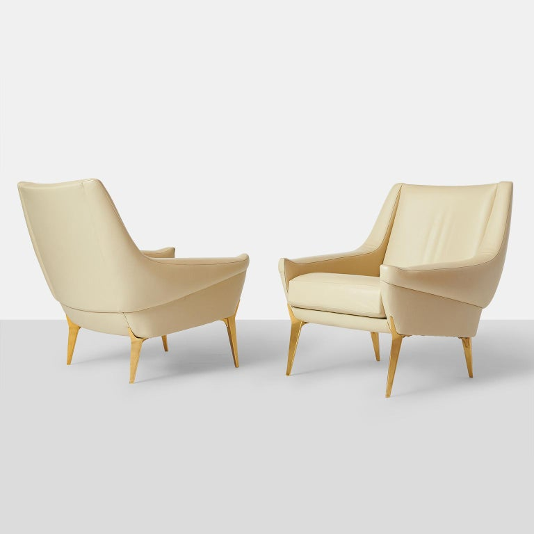 Pair of lounge chairs by Charles Ramos A rare set of lounge chairs in ivory leather with tapered gilt metal legs. Edited by Castellaneta France, circa 1950.
