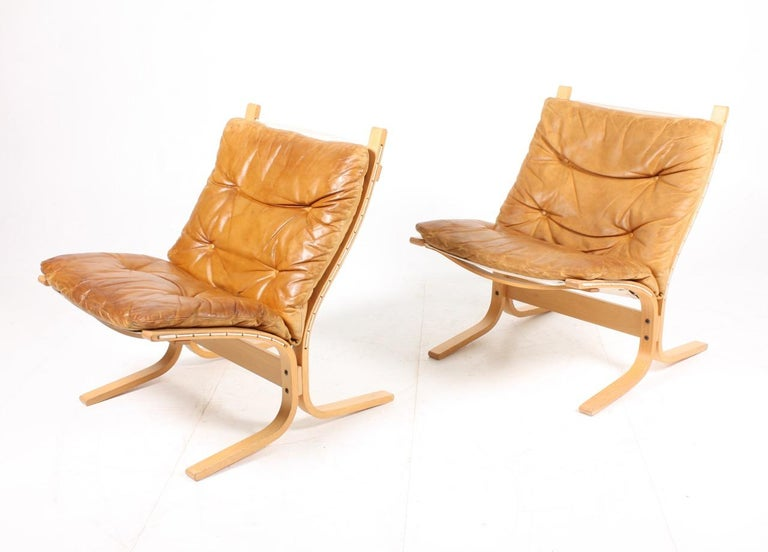 Pair of great looking lounge chairs in plywood and patinated leather designed by Ingmar Relling in 1965. Made in Norway. Great original condition.