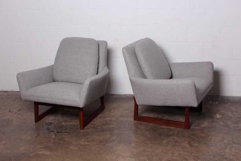 A pair of lounge chairs on walnut bases. Designed by Jens Risom and fully restored in Maharam wool.