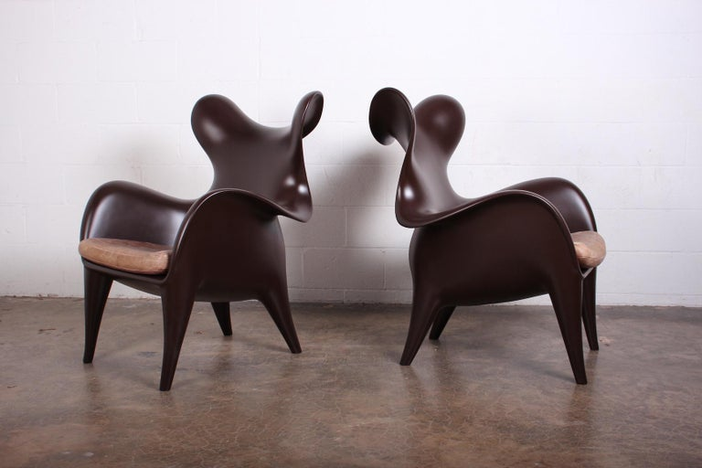 A pair of sculptural lounge chairs designed by Jordan Mozer for the Américas Restaurant in Houston, TX. These have been restored and color-matched to the original flat chocolate brown lacquer. The original leather cushions have a wonderful patina.