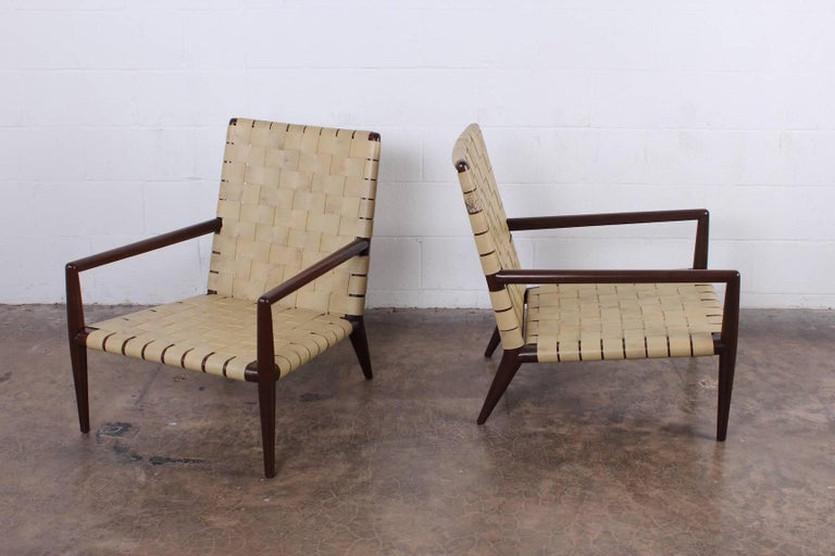 A pair of leather strapped lounge chairs with walnut frames. Designed by T.H. Robsjohn-Gibbings for Widdicomb.