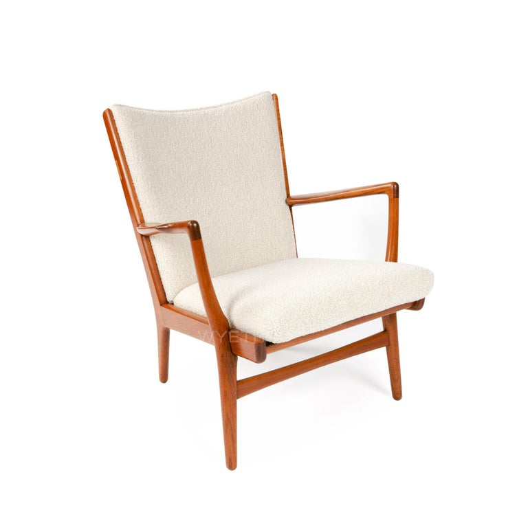 A pair of upholstered lounge chairs with teak frames.