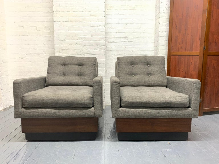 Pair of Mid-Century Modern lounge chairs. Has a walnut and black lacquered plinth base. Loose, tufted cushioned seat and back.