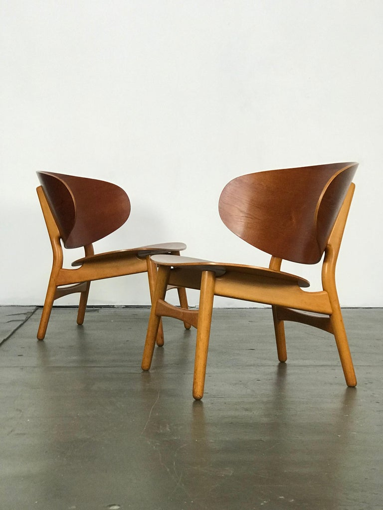 Important pair of Hans Wegner Shell lounge chairs. Designed in 1948. These have been recently restored, yet still show some age/wear. The chairs are made of beautiful contrasting wood types, teak and beech.
