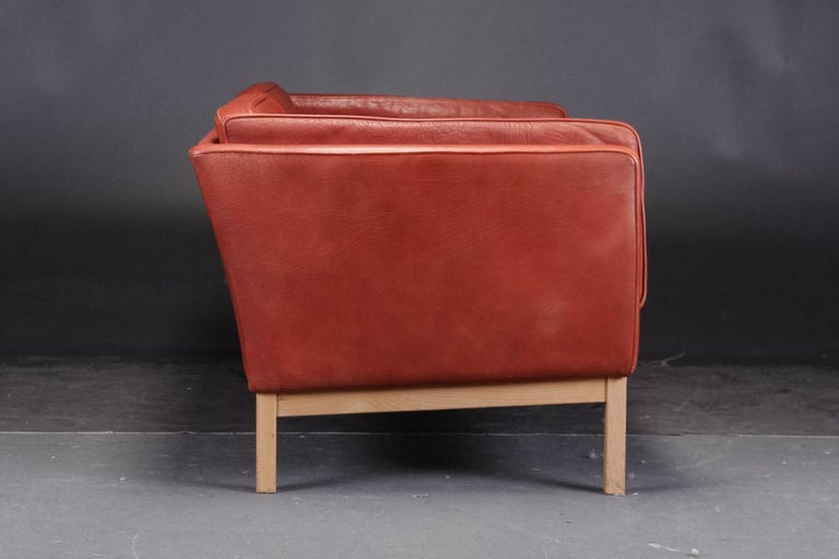 Pair of Danish modern loveseats by Vatne Møbler. Two-seat sofas, model 'Forum', loose cushions upholstered in patinated, deep red buffalo leather, deep-stitched back cushions, legs and solid ash frame. L. 145 cm. Sh. 43 cm. Slight traces of wear