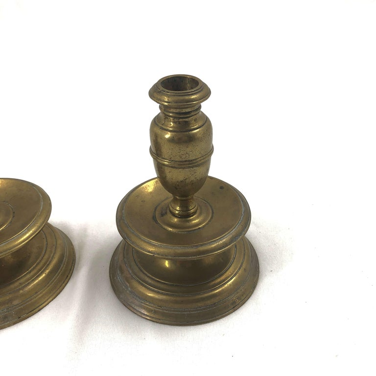 An early pair of brass capstan candlesticks with mid drip.
