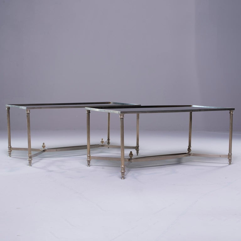 Pair of French circa 1940s pair of cocktail tables in the style of Maison Baguès feature silver tone metal frames with reeded legs and stretchers accented with finials. Inset black glass table tops. Sold and priced as a pair. Unknown maker.