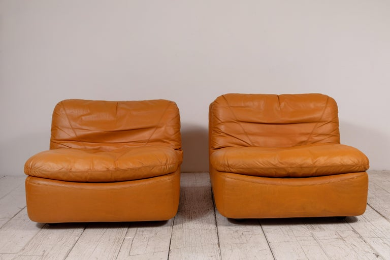This pair of low relaxed slouchy lounge chairs has boxed frame with comfy seat cushions that rest on top of the frame structure. The armless low chairs offer unique leather stitching. The design is very rare.