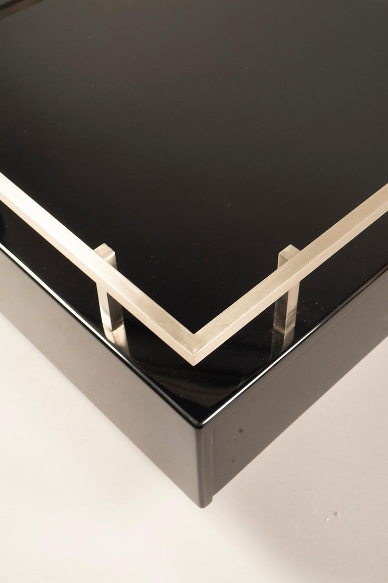 Square black lacquered tables with a raised aluminum frame supporting a glass top. The table bases feature a divided drawer.