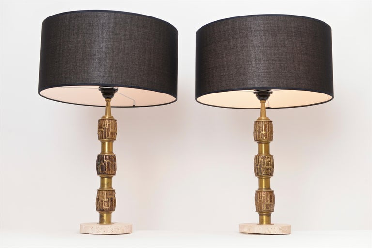 A lovely pair of 1970s Italian table lamps by Luciano Frigerio. Each of the lamps has three decorative ribbed sections in an abstract form which sit in a circular travertine base. The lamps have been completely re-wired and come complete with two