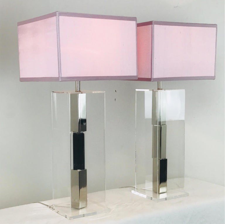 Pair of Lucite and chrome table lamps by Laurel. Chrome bars stacked in the center of a Lucite box.  New Pink Silk shades are included.  Dimensions: 7