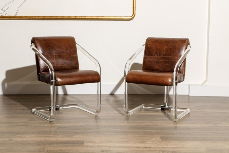 This gorgeous pair of lucite, leather and chrome armchairs by Lion in Frost (both chairs are signed), circa 1970s, are signed on the lucite post near the base and are in good vintage condition with lightly patinated and thick brown colored leather.