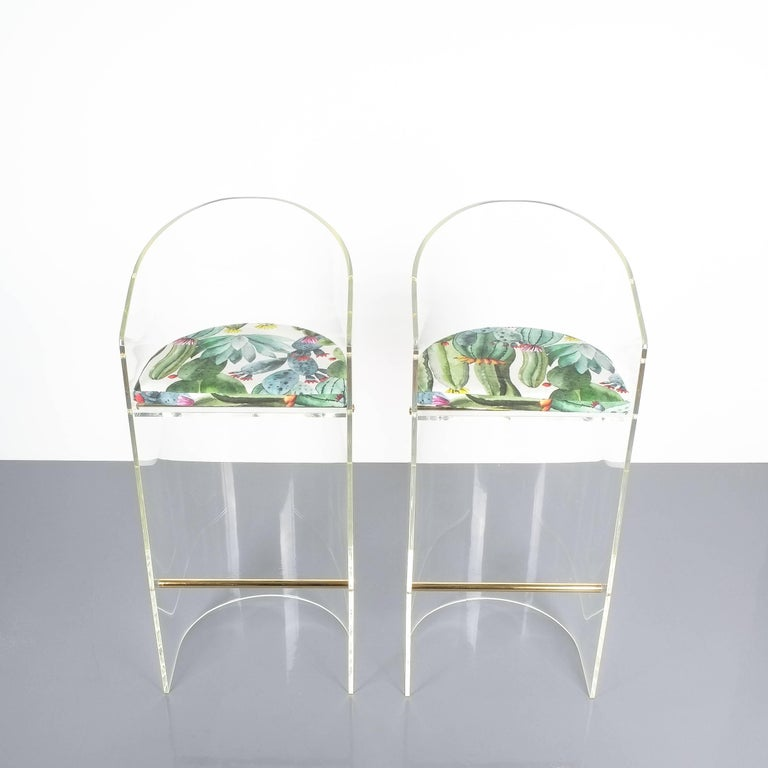 Pair of Lucite brass bar stools Style Charles Hollis Jones, 1960. Beautiful stools made from a single bend slab of perspex and brass details. Perfect for a kitchen. Both have been newly polished (brass and Lucite) and newly upholstered with
