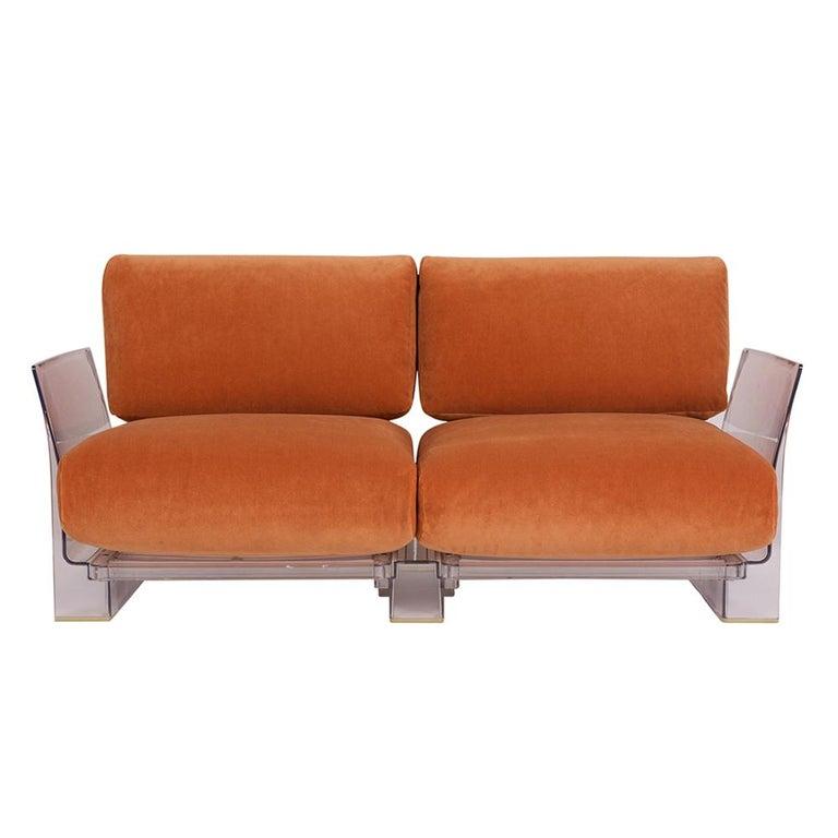 This pair of Lucite loveseats or sofas are designed by Piero Lissoni for Kartell. Each sofa features a stylish Lucite frame in great condition with 2 seat and back cushions. The cushions have been professionally reupholstered in an orange mohair