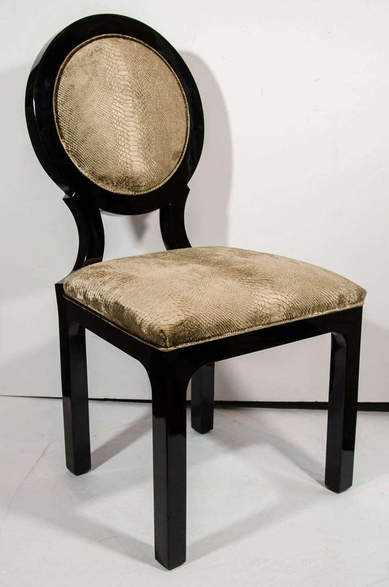 Art Deco side chairs with neoclassical inspired round back design. The chairs are finished in a rich black lacquer and have been upholstered in a luxe velvet-mohair fabric with an embossed python print pattern in vibrant hues of taupe or mushroom.