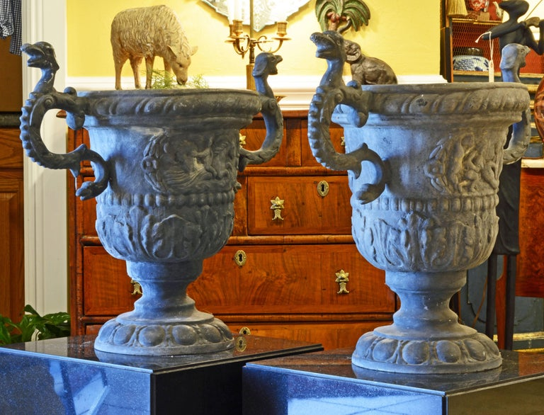 Standing 22 inches tall this pair of lead urns will be impressive both outdoors and indoors. The handles are fashioned as double headed serpents and the main body features classical mythological reliefs above archantus borders.