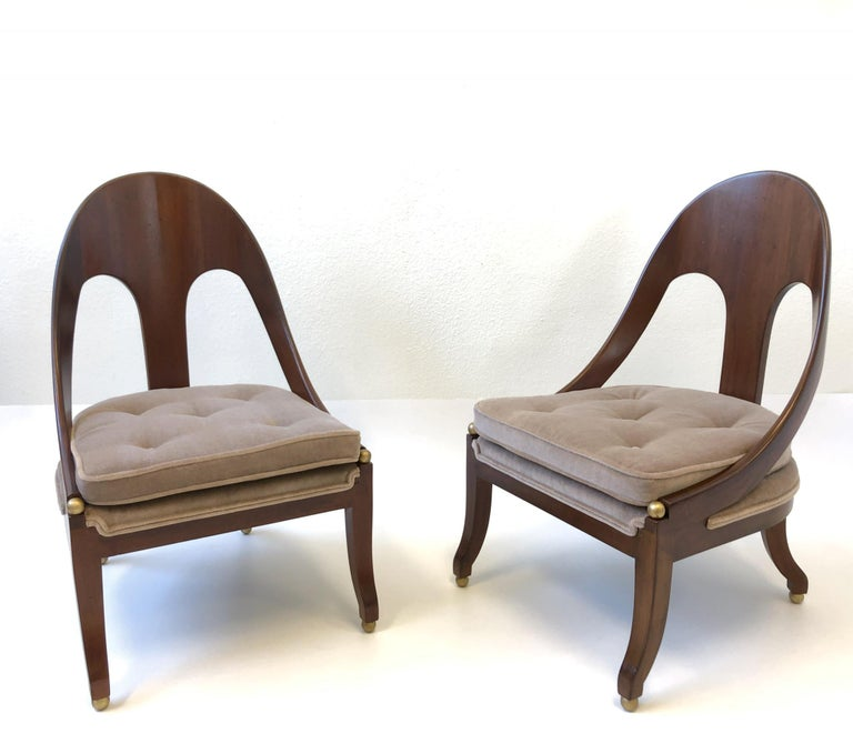 A spectacular pair of 1950s solid mahogany spoon back lounge chairs by renowned designer Michael Taylor for Baker Furniture Co. The spheres are gilded. Newly reupholstered in a soft light brown with a hint of blush mohair fabric. If you need a