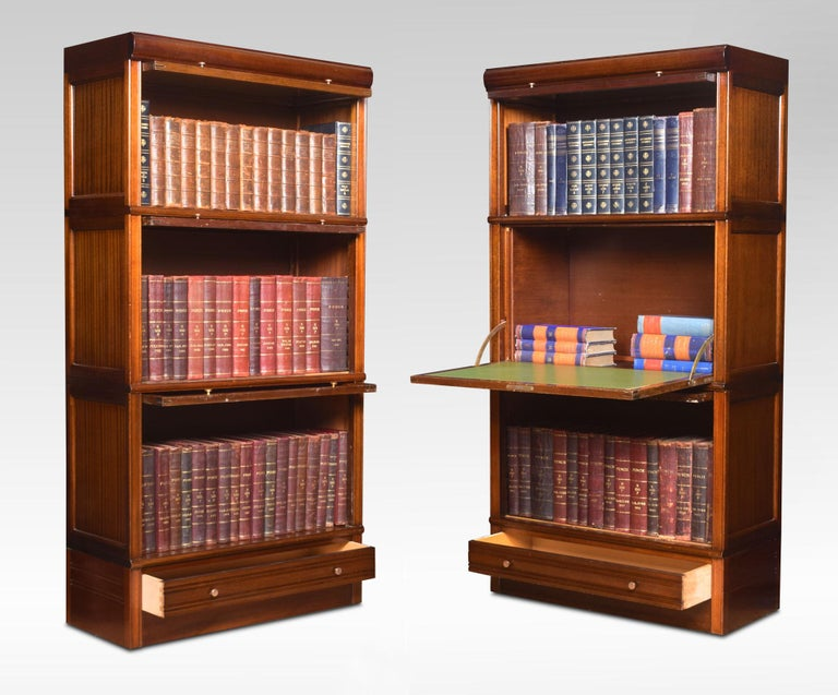 Pair of mahogany sectional bookcases. The moulded top above glazed doors and brass knobs, the next two sections having mahogany panelled doors one section fitted with inset green leather writing surface. To the base fitted with a single long