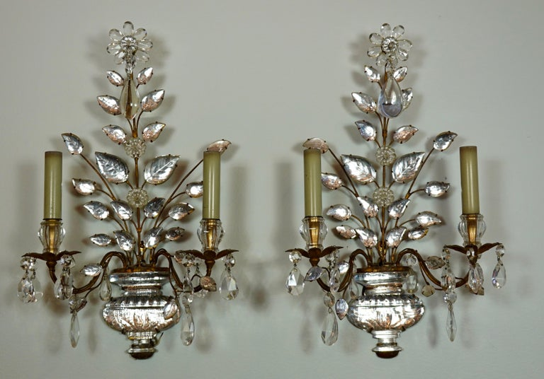 A pair of French gilt-iron and crystal two-arm sconces by Maison Bagues (mid-century). The sconces feature a hand-strung flower and spray of leaves planted in a crystal urn base. Crystal drops are suspended from the flower, bobesches and arms.