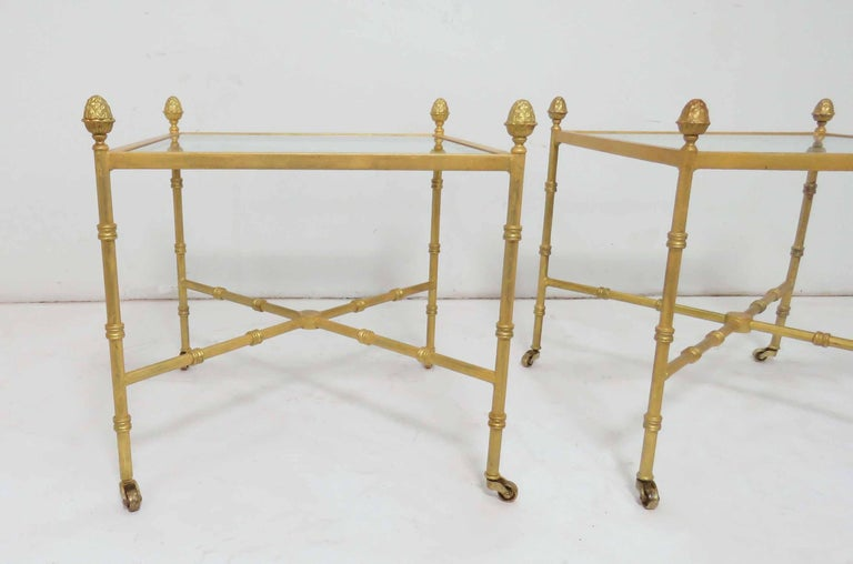 Pair of glass top end tables in gilt metal with acorn finial accents, X-form stretchers, and delicate solid brass casters.  Measures: 20.75