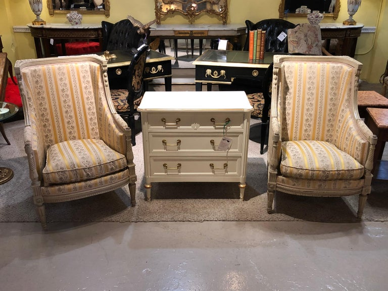 Pair of Maison Jansen attrib. Louis XVI Style French wingback or armchairs in a Swedish Finish. These tall and sleek impressive arm or office chairs are simply stunning depicting the finest quality carvings on the Swedish off white paint decorated