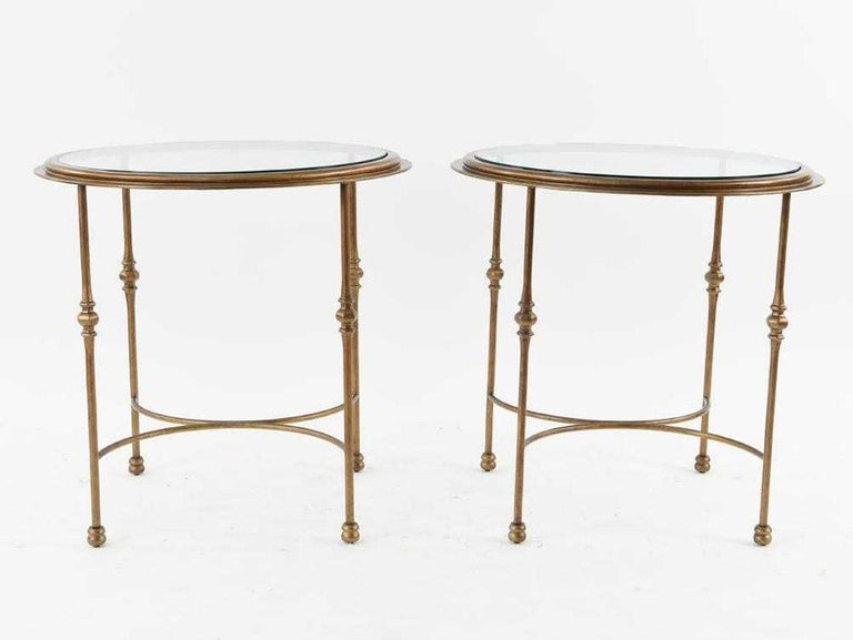 The pair of classical form circular gueridon with inset glass tops are made of patinated bronzed metal. Curved stretchers secure the decorative legs. Perfect as end or side tables for the sun room or porch. Small chip on the glass top and some