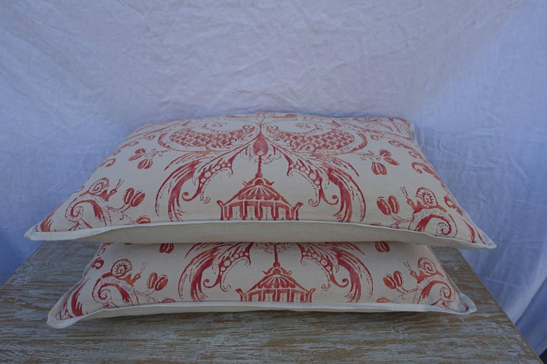 Pair of Manziano patterned Fortuny pillows in tangerine and cream coloration with cream colored linen backs and self welt detail. Down and feather inserts, sewn closed.