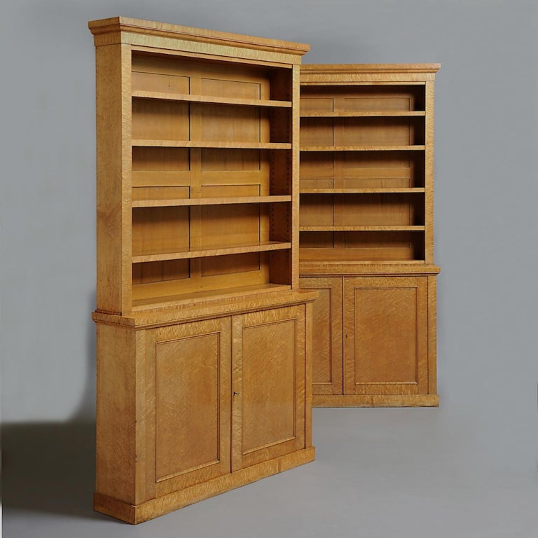 A fine pair of William IV burr maple open bookcases, each with adjustable shelves above two-panelled doors, circa 1830.