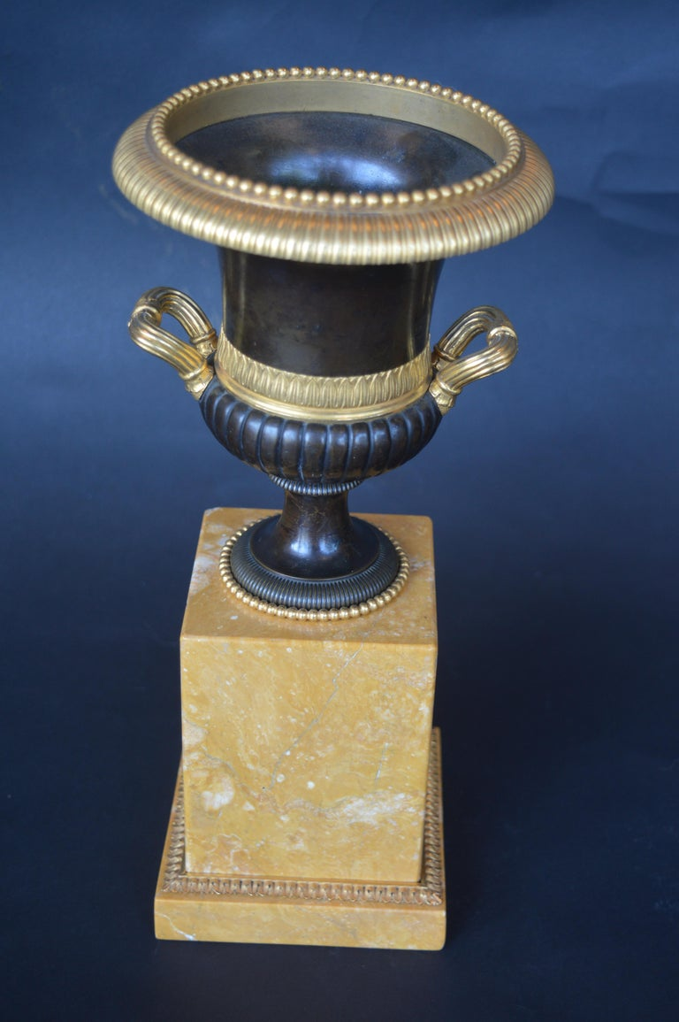 A pair of gilt, patinated bronze and marble campagna urn ornaments.