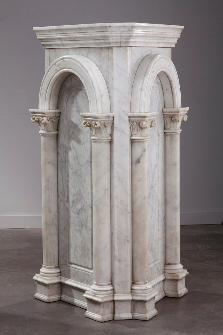 Mid-19th century pair of neoclassical white marble pedestals designed in an architectural manner. The entablature of each stand is supported by an arch, and the arch supported by two columns with Corinthian capitals. The scheme is classical,