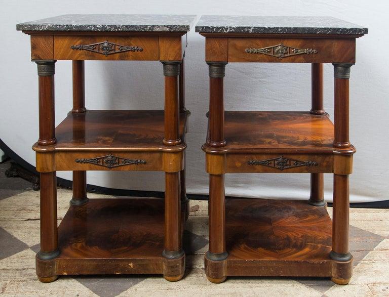 Veined black marble tops, separate. Mahogany tables. Single drawer below the top. Mid shelf below, platform base. Bronze mounts on drawers and columns. Bun feet.