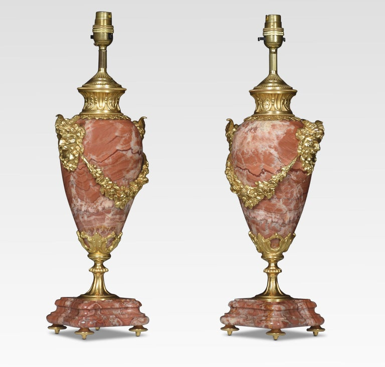 Pair of gilt brass mounted rouge marble table lamps with satyr mask handles and floral swags raised up on shaped stepped bases. Together with silk shades.