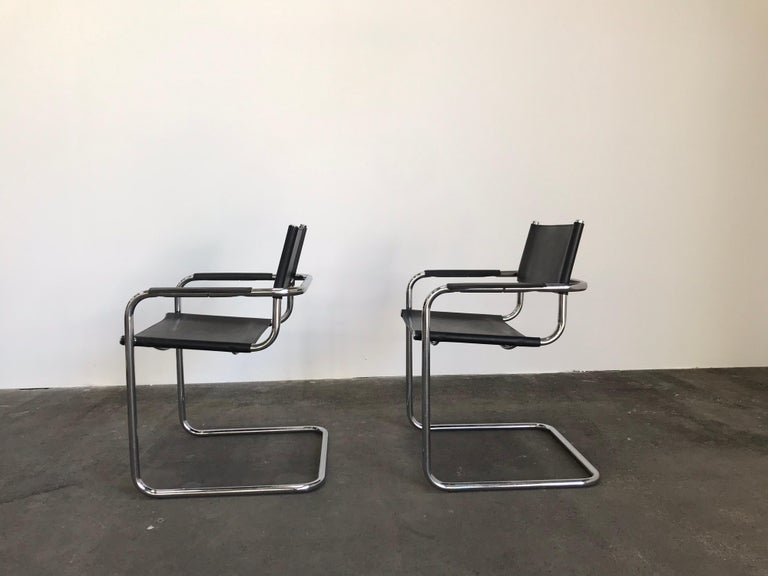 Iconic Bauhaus design by Marcel Breuer. These dining chairs are cantilevered tube steel with black leather seat, backrest and armrest covers.  Model B34 / MG5 by Matteo Grassi / Thonet.