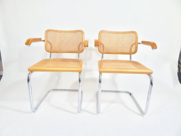 Midcentury pair of Marcel Breuer Cesca chairs, 1970s production. Both marked Made in Italy. Good original condition. Some wear to armrests. Additional measurement: Top of armrest to floor 27.25.