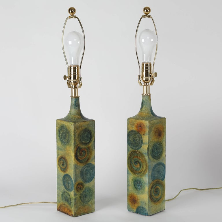 Fine pair of 1960s ceramic table lamps by noted Italian designer Marcello Fantoni. The square bases are hand-painted in blue-green and embellished with circles in blue and rust. Three-way switch on neck; standard-base socket. New polished-brass