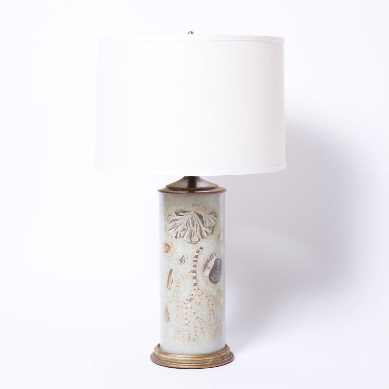 Unique pair of glass cylinder table lamps with marine shell and sea life inspired reverse elgomise decoupage against a sea green background.
