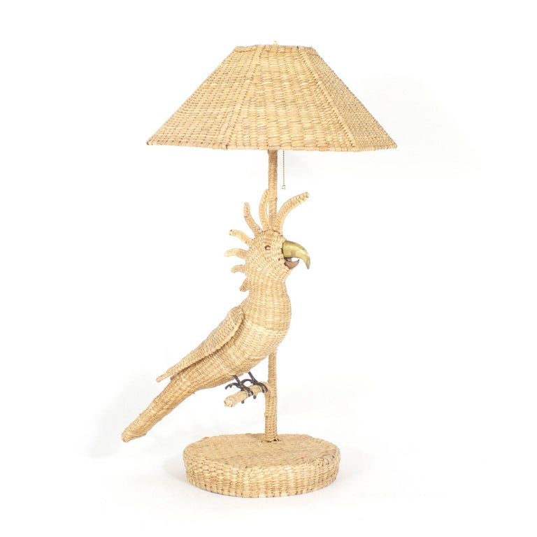 Pair of Mario Torres table lamps depicting cockatoos perched on a branch with brass and copper beaks and copper eyes. Constructed of a metal frame tightly wrapped in wicker or reed with matching wicker shades. Signed Mario Torres Established 1974 on