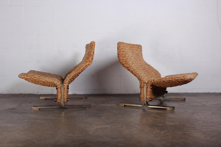 A pair of lounge chairs with solid patinated brass bases and woven rope seats. Designed by Marzio Cecchi.